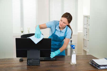 オフィスでデスクトップ コンピューターを消毒用の作業服の若い女性