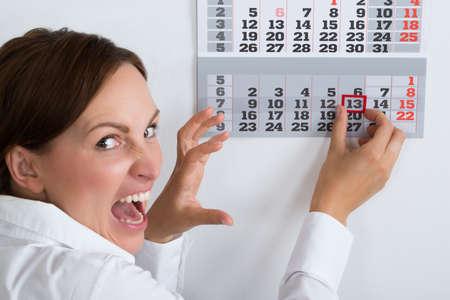 Close-up Of Frightening Businesswoman Marking Friday 13 On Calendar