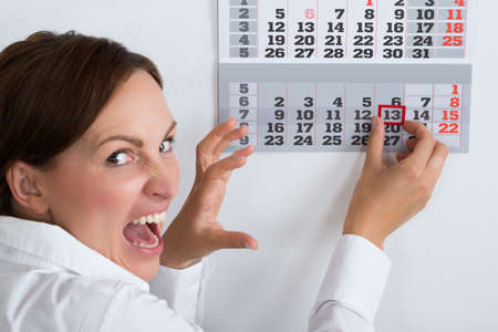 Close-up Of Frightening Businesswoman Marking Friday 13 On Calendar