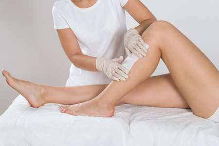 Beautician Waxing Leg Of Woman With Wax Strip At Beauty Clinic