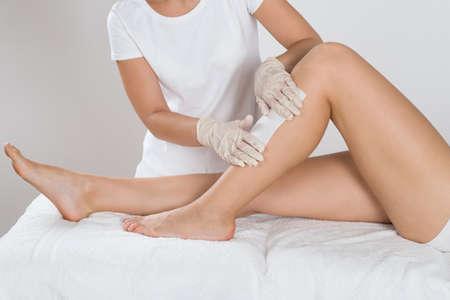 Kosmetikerin Waxing Bein der Frau mit Wachs-Streifen an Beauty Clinic