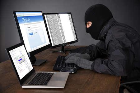 hacker: Hacker Wearing Balaclava Hacking Computers At Desk