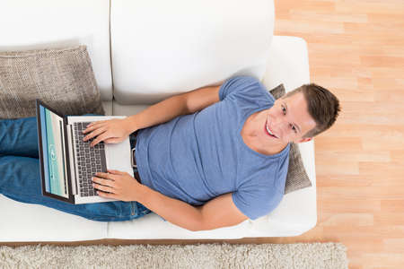 man with laptop: High Angle View Of Young Man Watching Video On Laptop At Home