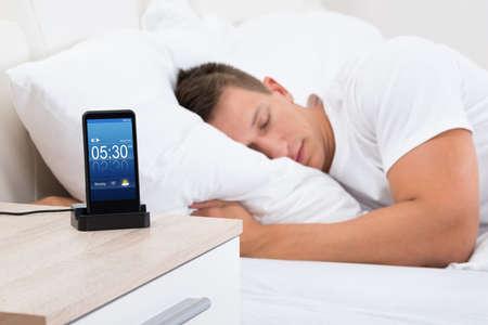 despertador: Hombre joven que duerme en cama con la alarma en la pantalla Tel�fono m�vil Foto de archivo