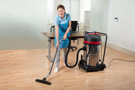 mujer limpiando: Happy Female Worker Cleaning Floor With Vacuum Cleaner In Office