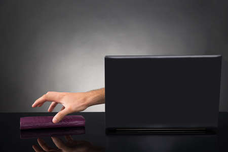 scammer: Close-up Of Person Hands Reaching Out From A Laptop Grabbing Wallet At Desk Stock Photo
