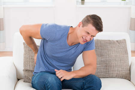 man back pain: Young Man On Sofa Suffering From Backpain At Home Stock Photo