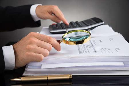デスクの虫眼鏡と請求書をチェックの実業家の手のクローズ アップ