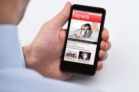 read news: Close-up Of Businessperson Reading Online News On Mobile Phone