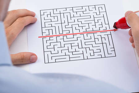 writing lines: Close-up Of Person Drawing Straight Red Line Over Maze With Red Marker Stock Photo