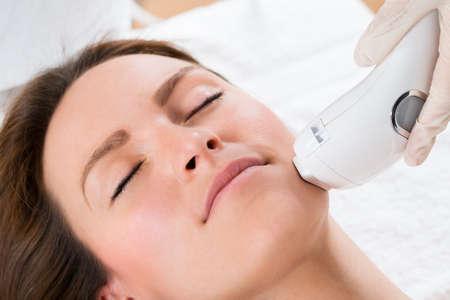 Close-up Kosmetikerin, die Haarentfernung mit Laser-Behandlung Um junge Frau Gesicht Lizenzfreie Bilder