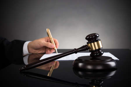 trial indoor: Close-up Of Judge Hands Writing On Paper With Pen And Gavel In Courtroom