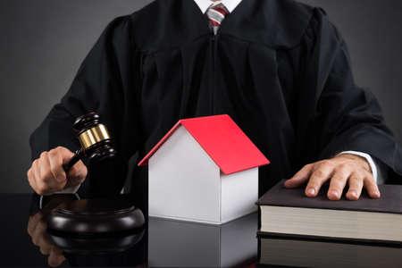 divorcio: Primer De La juez sostiene el mazo con la casa modelo en el escritorio