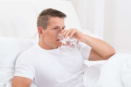 tomando refresco: Hombre joven que se sienta en la cama de Agua Potable Foto de archivo