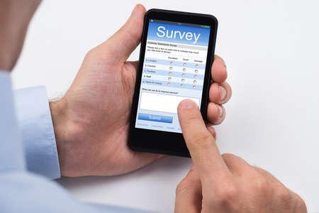 Close-up Person Ausf�llen von Online-Umfrage-Formular auf Handy Lizenzfreie Bilder