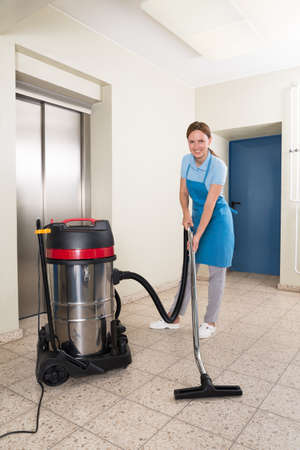 janitor: Young Female Janitor Cleaning Floor With Vacuum Cleaner