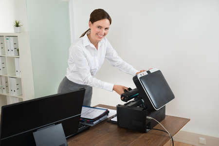 printer cartridge: Young Happy Businesswoman Holding Laser Cartridge With Printer At Desk