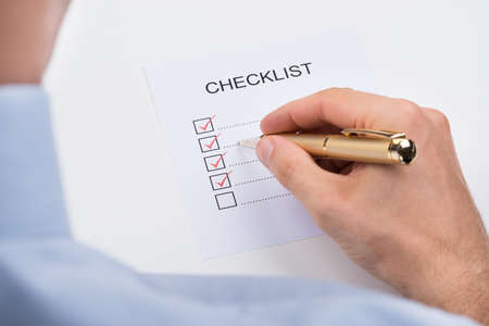 hand pen: Close-up Of Person Filling Checklist Form With Pen