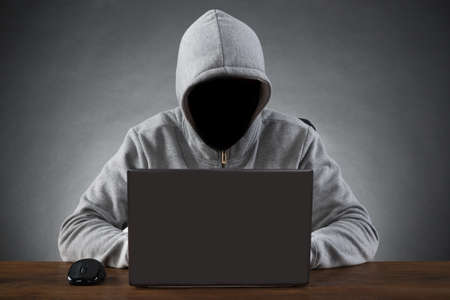 internet fraud: Hacker In Hood Jacket Using Laptop At Table
