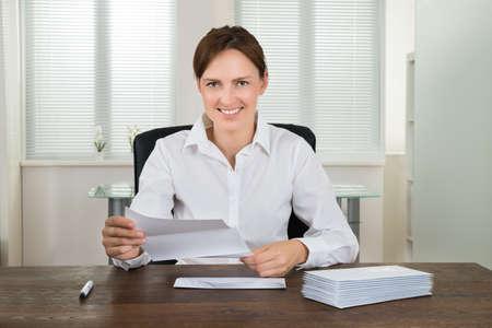 apilar: Joven empresaria titulares de un documento con la pila de sobres en el escritorio en la oficina