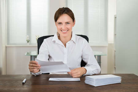 stacks: Young Happy Businesswoman Holding Document With Stack Of Envelopes At Desk In Office
