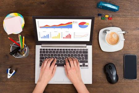 Erhöhte Ansicht der Person Analyse Statistische Grafiken an Laptop auf Schreibtisch Standard-Bild - 45165799