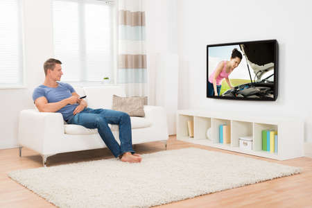 Young Man With Remote Control Watching Television In Living Room