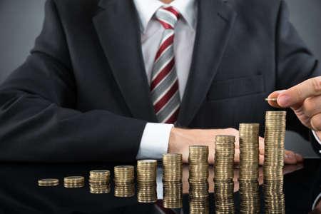 Close-up der Geschäftsmann Platzieren Münze über Stapel Münzen am Schreibtisch