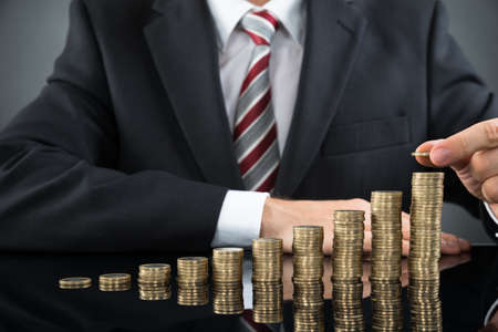 stack of cash: Close-up Of Businessman Placing Coin Over Stack Of Coins At Desk Stock Photo