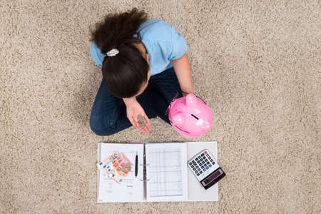 inserting: Woman Sitting On Carpet With Invoices And Money Inserting Coin In Piggybank Stock Photo