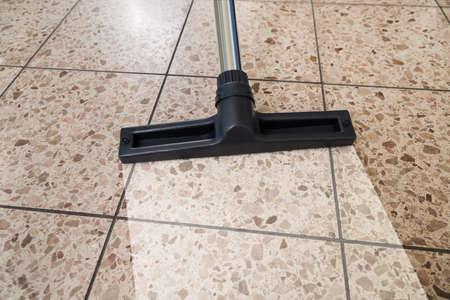 Close-up Of Vacuum Cleaner Over Cleaned Floor Foto de archivo