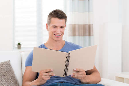 man looking: Portrait Of Young Happy Man With Photo Album Sitting On Sofa Stock Photo