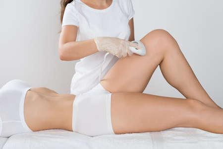 depilacion: Primer plano de joven con el tratamiento con láser en el muslo En la Clínica de Belleza Foto de archivo