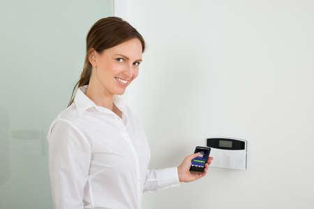 Jonge zakenvrouw die Entree Security System met mobiele telefoon