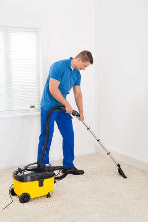 servicio domestico: Feliz masculino Conserje Limpieza de alfombras con aspiradora Foto de archivo