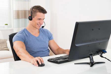 uomo felice: Uomo Felice Utilizzando computer desktop e auricolare a casa
