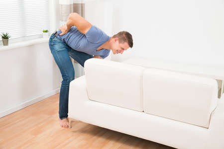 Young Man Suffering From Backpain While Lifting Sofa In Living Room Stock Photo
