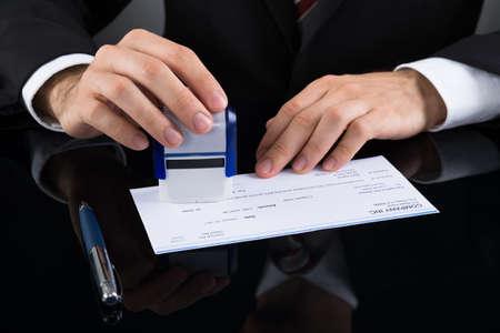 Close-up Van Zakenman Stamping Cheque Bij Bureau