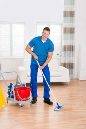 hardwood floor: Happy Worker With Cleaning Equipments And Wet Floor Sign In House