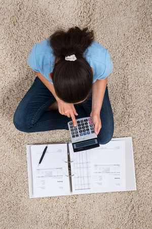 calculating: Young Woman Sitting On Carpet Calculating Invoices With Calculator