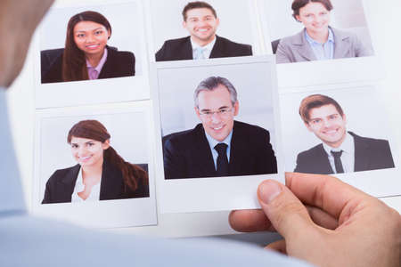 candidates: Close-up Of Businessperson Choosing Photograph Of Best Job Candidate