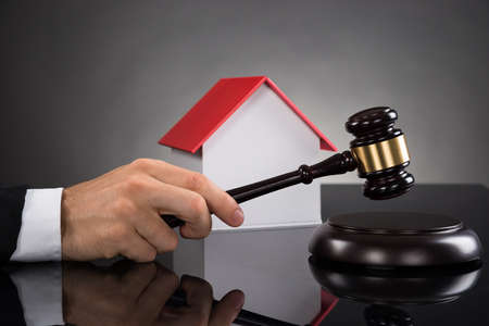 courtroom: Close-up Of Judge With House Model Hitting Gavel At Desk Stock Photo