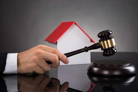 Nahaufnahme des Richters mit Haus Modell Schlagen Hammer Am Schreibtisch Standard-Bild