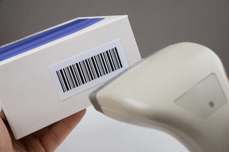 barcode scanner: Close-up Of Person Hands Using Barcode Scanner To Scan A Barcode On A Box