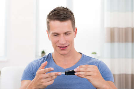 glucometer: Close-up Of Young Happy Man Checking Blood Sugar Level With Glucometer