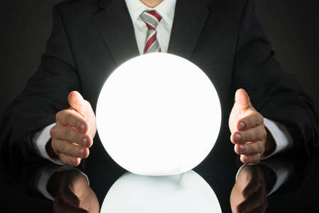 foreshadow: Close-up Of Businessman Predicting Future With Crystal Ball At Desk Stock Photo