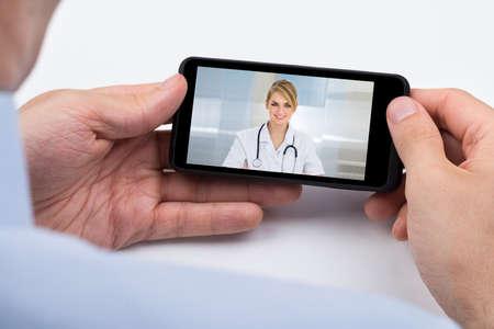llamando: Primer De La Persona Videochatting Con Doctora en el teléfono móvil Foto de archivo
