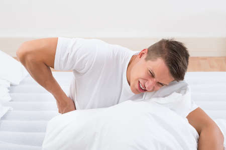 backpain: Young Man On Bed Suffering From Backache Stock Photo
