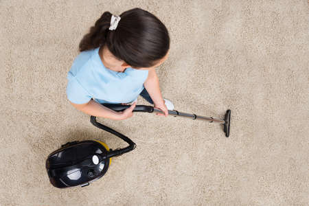 apartment cleaning: High Angle View Of Woman Cleaning Carpet With Vacuum Cleaner