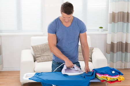 house cleaning: Young Happy Man Ironing Clothes On Ironing Board